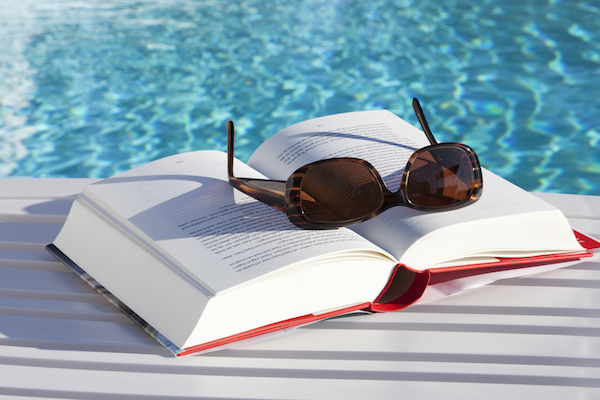 Book and sunglasses on a sunlounger by the swimmingpool